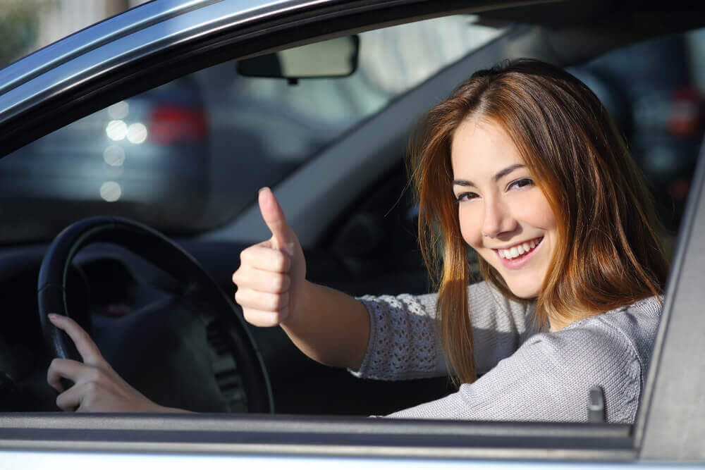 young female learner driver giving the thumbs up out of a window after a successful driving test